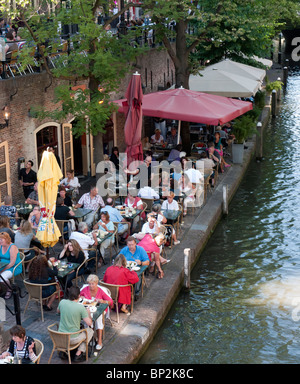 Busy outdoor summer cafes and restaurants beside canal Oudegracht in central Utrecht in the Netherlands - Stock Photo