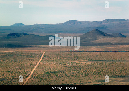 aerial view above freight train passing through New Mexico - Stock Photo