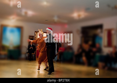 Senior citizen lady with Rudolph costume wearing a bright red nose, dances in a ballroom dance event. - Stock Photo