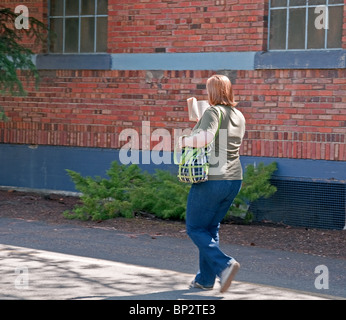 This woman is an avid reader as she reads a book while walking along a pathway against a beautiful old brick building. - Stock Photo