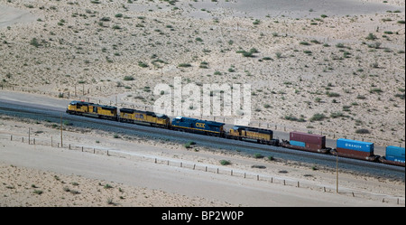 aerial view above freight train passing through desert New Mexico - Stock Photo