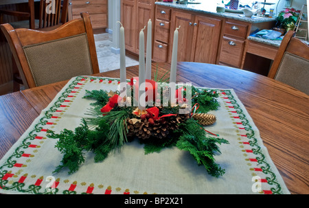 Christmas table centerpiece with evergreen boughs, pinecones, red ribbon, a large round red candle &several white - Stock Photo