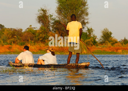 Poler with tourists in a traditional mokoro logboat on excursion in the Okavango Delta, Botswana - Stock Photo
