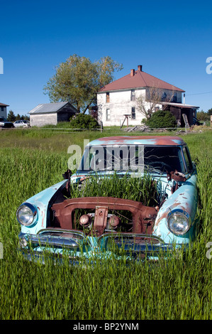 Abandoned overgrown car in a field at old western town of Flora, Oregon. - Stock Photo