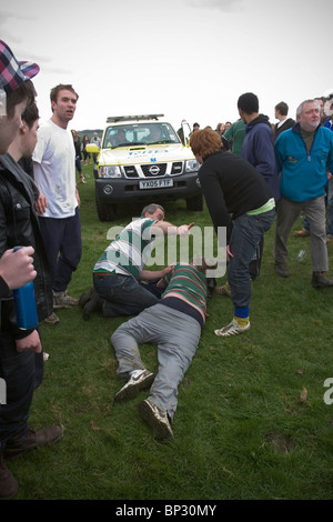 Man lying on floor awaiting medical attention after being trampled during traditional game of Bottlekicking, Leicestershire, - Stock Photo