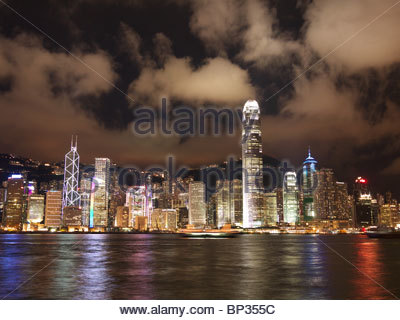 Hong Kong island skyline at night viewed from Kowloon with clouds and refections of bright lights in the water of - Stock Photo