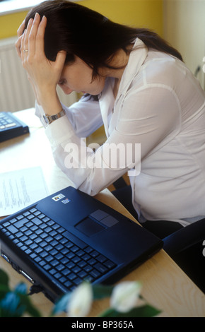 pregnant woman feeling ill at work holding her head in her hands by her computer - Stock Photo