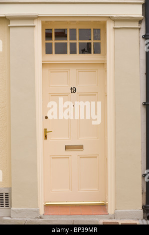 Painted cream coloured wooden paneled front door no. 19 with brass handle letterbox and fanlight of period town - Stock Photo
