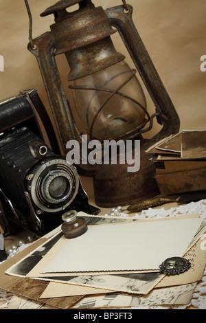 Retro camera, kerosene lamp and old photos on the knitted cloth - Stock Photo