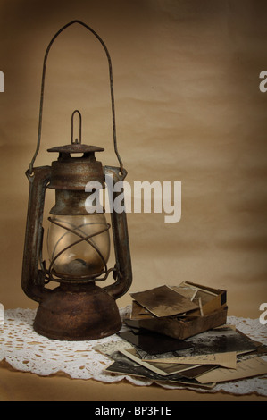 Old kerosene lamp and photos on the cloth - Stock Photo