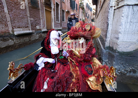 Costumed models during Carnival in Venice, Italy in a gondola - Stock Photo