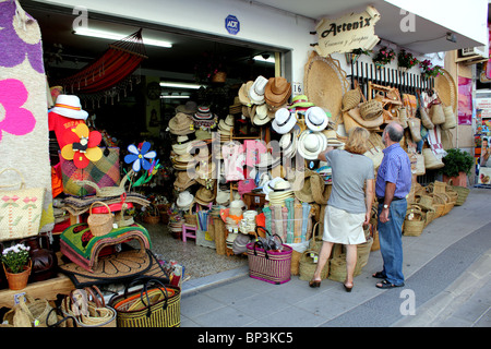Man and woman tourist looking at crafts and handicrafts displayed outside a shop in Nijar, near Almeria Andalucia - Stock Photo
