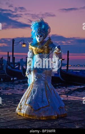 Costumed model during Carnival in Venice, Italy at sunrise - Stock Photo