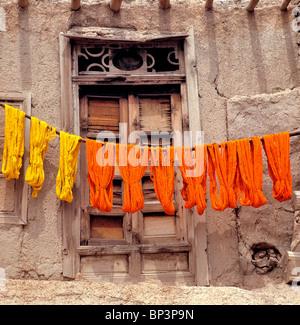 Afghanistan, Ghazni. Colorful woolen yarn dries on wooden poles in Ghazni in Afghanistan. - Stock Photo