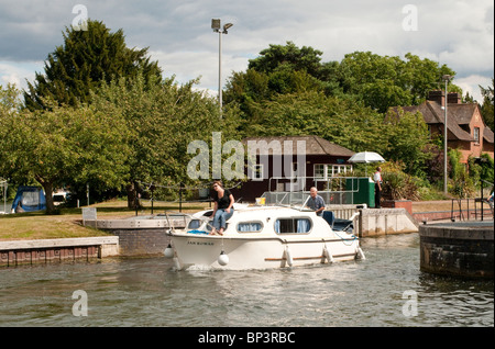 Boat Leaving Hambleden Lock River Thames on a sunny day in August - Stock Photo