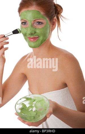 Attractive woman applying green facial mask on white background - Stock Photo