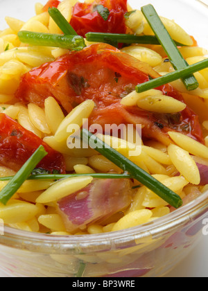Orzo rice shaped pasta sun dried tomato salad in glass bowl on a white background - Stock Photo