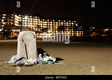 Overflowing rubbish container on beach in Spain with large hotel in background - Stock Photo