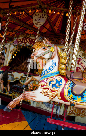 Steam Galloping horse carousel fairground ride at a  steam fair in England - Stock Photo