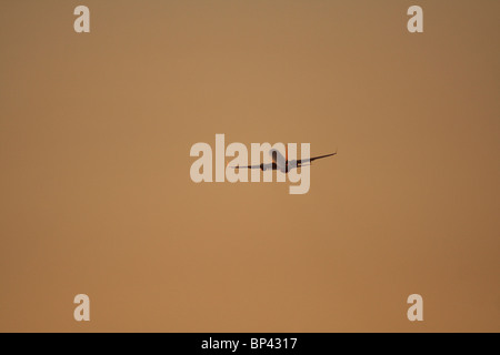 Commercial air travel. Passenger jet plane flying in the sky at sunset with copy space. Proprietary details deleted. - Stock Photo