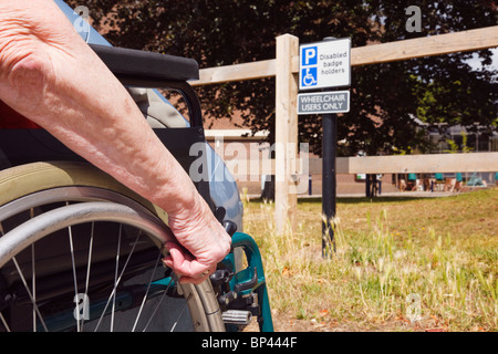 Elderly woman sitting in a wheelchair by a car parked in disabled parking bay by a sign for blue badge wheelchair - Stock Photo