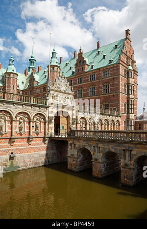 The entrance to the Frederiksborg Castle in Dutch Renaissance style over the moat in Hillerød near Copenhagen, Denmark. - Stock Photo