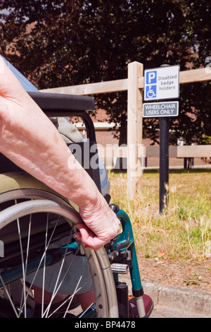 Elderly woman sitting in a wheelchair by car parked in blue badge disabled parking bay by a sign for wheelchair - Stock Photo