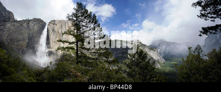 A view across Yosemite valley with clouds in the background and upper Yosemite falls in the foreground - Stock Photo