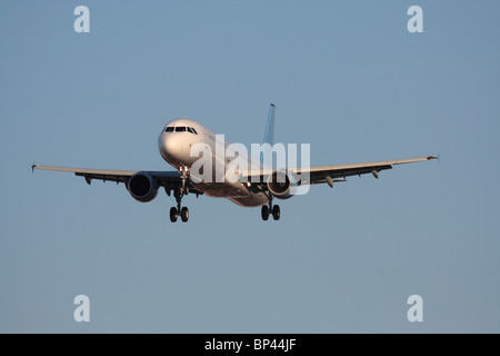 Commercial air travel. Airbus A321 narrowbody passenger jet plane flying on approach in a blue sky. Front view with - Stock Photo