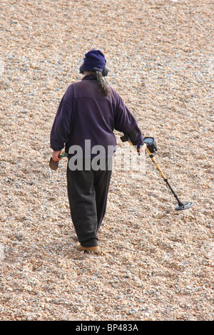 A man with a metal detector on Brighton beach. - Stock Photo