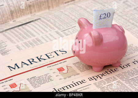 pink piggy bank with 20 pound note sitting on a copy of the financial times newspaper money markets section in the - Stock Photo