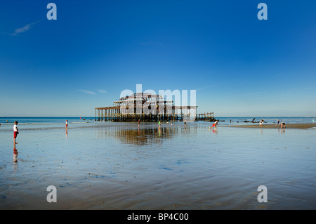 Playing cricket at low tide on the sandy beach in front of the Brighton derelict West Pier - Stock Photo
