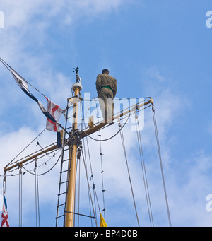 crewman standing on the top yard of the rear mast of a barquentine sailing ship (The Dewaruci) - Stock Photo