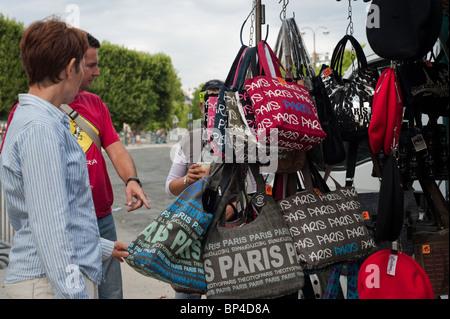 Paris, France, Tourist Couple near Eiffel Tower, Buying Souvenir Bags - Stock Photo