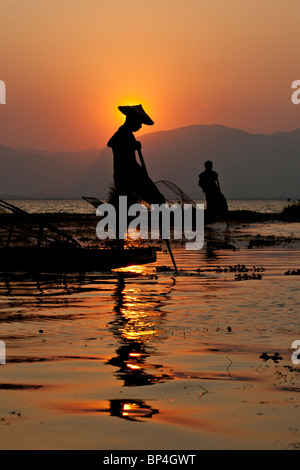 Fishermen on Inle Lake in Myanmar casting their conical nets into the water as the sun sets behind them. - Stock Photo
