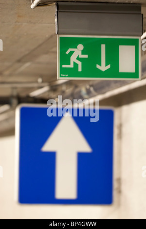 Blue traffic sign with a white arrow pointing up and an emergency exit sign with arrow pointing down - Stock Photo
