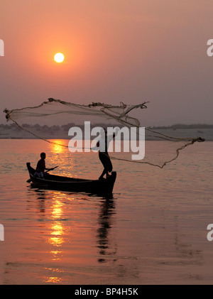 A fishing family works together to catch fish on the Irrawaddy River at dusk near Mandalay, Myanmar. - Stock Photo