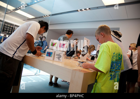 People try out the iPad in an Apple store in Los Angeles, California, USA. - Stock Photo