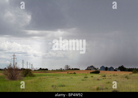 Rain pouring down onto farmhouse and silos in a thunder storm in rural farmland of southwest Colorado - Stock Photo