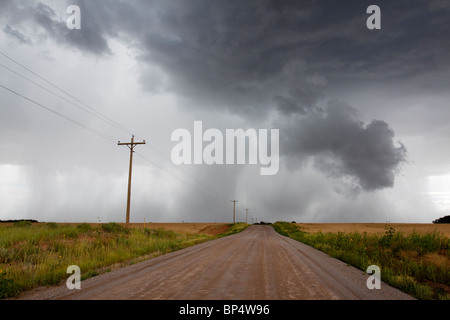 Angry looming cumulus thunder storm clouds releasing rain in a rural thunderstorm with dirt road leading into distance - Stock Photo