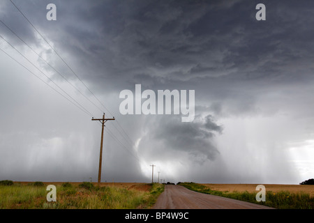 Angry looming cumulus thunder storm clouds releasing rain in a rural thunderstorm with dirt road leading into the - Stock Photo