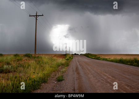Rural thunderstorm scene - dirt road leads to bright light in sky between dark  looming cumulus thunder clouds releasing - Stock Photo