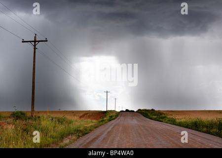Rural thunderstorm scene - dirt road leads to bright light in sky between dark  looming cumulus thunder clouds releasing - Stock Photo