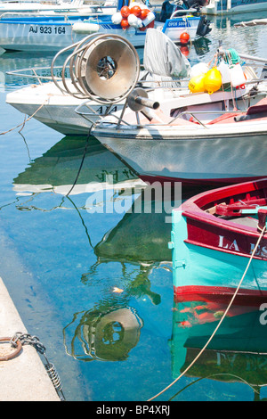 Local fishing boats reflected in the crystal-clear waters of the Old Port, Ajaccio, Corsica, France - Stock Photo