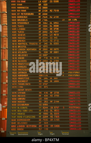 Passengers look at the departures board at Charles de Gaulle Airport in Paris, filled with cancelled or postponed - Stock Photo