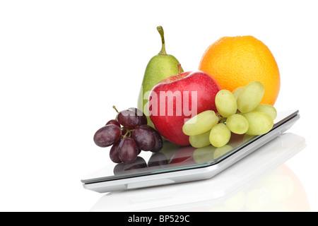 Apfel, Orange, Birne und Trauben auf einer schmalen Küchenwaage - Stock Photo