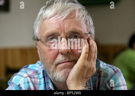 Grumpy old man with hand on chin wearing spectacles glasses - Stock Photo