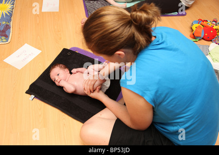 Baby massage. - Stock Photo