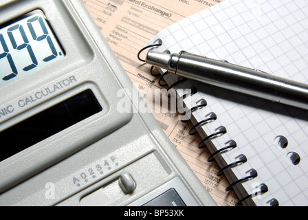Calculator with numbers on display, pen and notebook laying on newspaper. - Stock Photo
