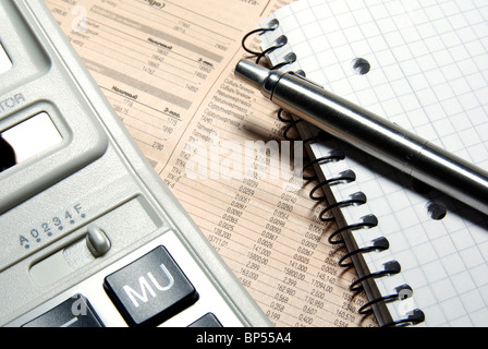 Financial calculator, steel pen and notebook laying on newspaper. Concept. - Stock Photo